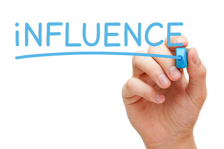 influencer: Hand writing Influence with blue marker on transparent wipe board. Stock Photo