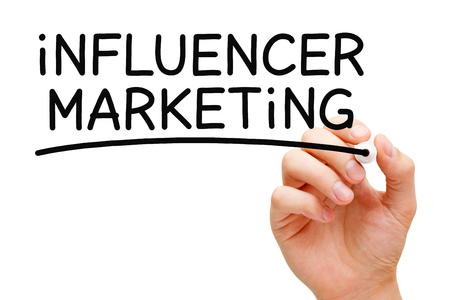 influencer: Hand writing Influencer Marketing with black marker on transparent wipe board.