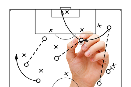 Coach sketching a football game strategy with marker on transparent wipe board. Soccer coach explaining game tactics.