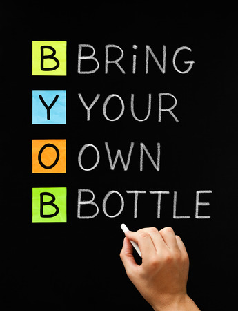 bring: Hand writing BYOB Bring Your Own Bottle with white chalk on blackboard. Acronym often used on party invitations where the alcohol is not provided and you have to bring your own.