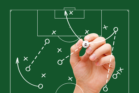 Manager drawing soccer game tactics with white marker on transparent wipe board over green background. Football coach explaining game strategy.