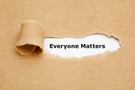 everyone: The text Everyone Matters appearing behind ripped brown paper.
