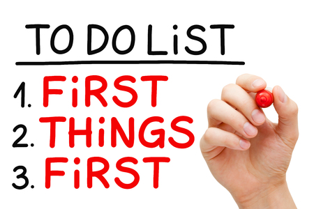 things to do: Hand writing First Things First in To Do List with red marker isolated on white.