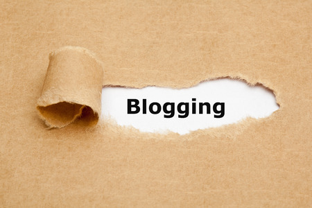 appearing: The word Blogging appearing behind ripped brown paper.