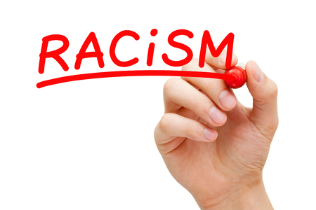 racismo: El racismo mano escrito con marcador rojo en la placa transparente limpie. Foto de archivo
