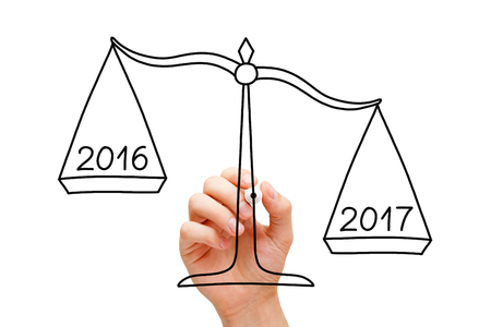 next year: Hand drawing scale concept with marker on transparent wipe board isolated on white. Year 2017 is better than 2016.