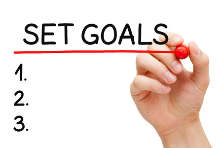 achievable: Hand writing Goals setting list with marker on transparent wipe board. Stock Photo