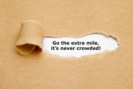 Motiverend citaat Go The Extra Mile It's Never Crowd verschijnen achter gescheurd bruin papier.