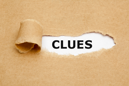 clues: The word Clues appearing behind ripped brown paper.