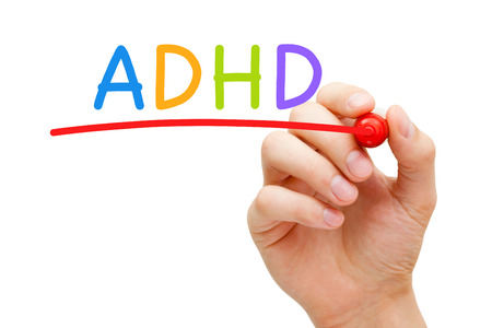 Hand writing ADHD Attention Deficit Hyperactivity Disorder with marker on transparent glass board. Stock Photo