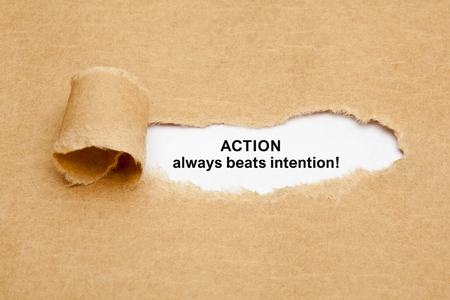 advice: Quote Action Always Beats Intention, appearing behind ripped brown paper. Stock Photo