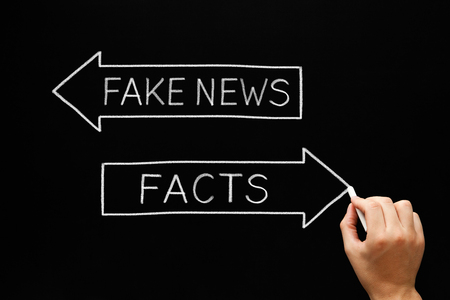 disinformation: Hand sketching Fake News or Facts concept with white chalk on blackboard.  Stock Photo