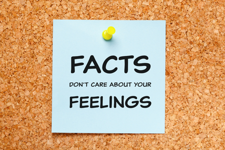 Quote Facts Do Not Care About Your Feelings handwritten on blue sticky note pinned on cork bulletin board.