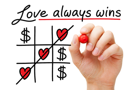 Hand drawing Love Always Wins over money tic tac toe concept with marker on transparent glass board isolated on white.