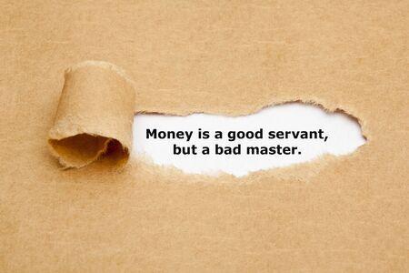 La cita Money es un buen sirviente pero un mal amo, que aparece detrás de un papel marrón rasgado. Foto de archivo