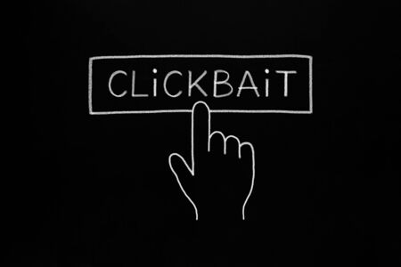 Hand cursor clicking Clickbait button drawn concept with white chalk on blackboard.