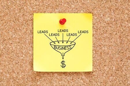 Lead generation sales funnel business concept drawn on yellow sticky note pinned on cork bulletin board.