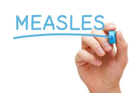 Hand writing the word Measles with blue marker on transparent wipe board isolated on white.