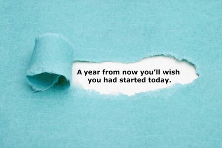 Motivational quote A year from now you will wish you had started today appearing behind torn blue paper. Stock Photo