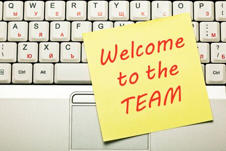 Text Welcome to the Team handwritten on yellow sticky note on laptop keyboard. Stock Photo