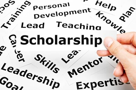 Hand holding a piece of paper with the word Scholarship printed on it above other related words in the background. Stock Photo
