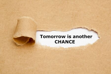 Motivational quote Tomorrow Is Another Chance appearing through a hole in torn brown paper.