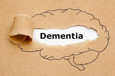 Word Dementia appearing behind ripped brown paper in human brain drawing.