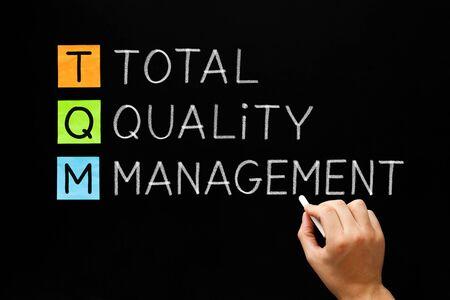 Handschrift Akronym TQM Total Quality Management Konzept mit weißer Kreide auf Tafel.