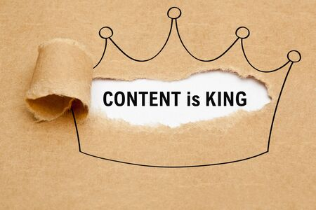 Text Content is King appearing behind torn brown paper in crown drawing. Concept about the importance of Content in internet marketing.