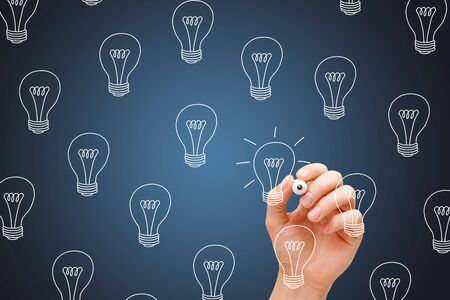 Hand drawing a light bulbs concept about choosing the best idea among many others with white marker.