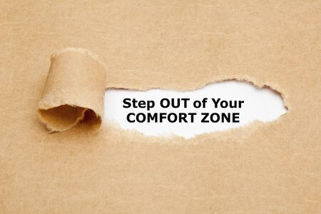Motivational quote Step out of your comfort zone. appearing behind ripped brown paper.