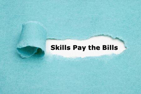 Printed text Skills Pay the Bills appearing behind torn blue paper. Zdjęcie Seryjne