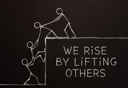 Quote We Rise By Lifting Others handdrawn on altruism, kindness, unselfishness, or teamwork concept drawn with chalk on blackboard.