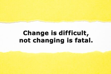 Motivational quote Change is Difficult not Changing is Fatal appearing behind torn yellow paper. Adaptation concept. 版權商用圖片