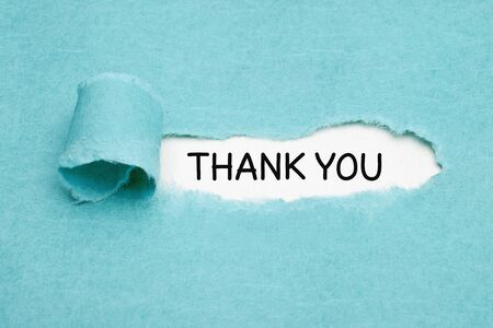 Handwritten text Thank You appearing behind ripped blue paper. Appreciation, gratefulness, or thankfulness concept.