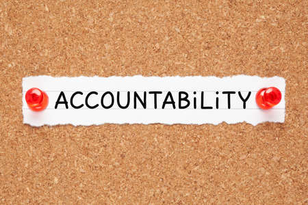 The word Accountability handwritten on a piece of white paper pinned on cork bulletin board.