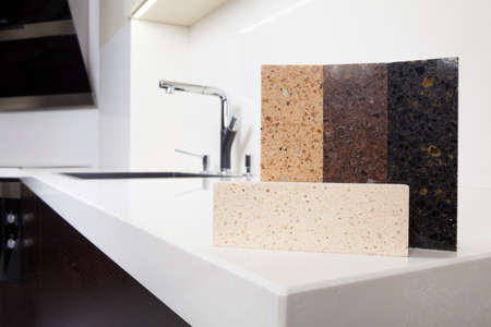 Different quartz kitchen counter top samples on white polished countertop with precise processed edges. Standard-Bild