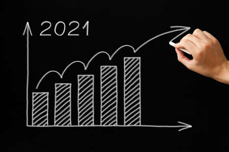 Hand drawing optimistic increasing growth graph for year 2021 with white chalk on blackboard. Recovery after financial crisis concept. Banque d'images