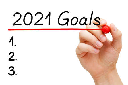 Blank goals list concept for year 2021 isolated on white background. Hand underlining 2021 Goals with red marker on transparent wipe board.