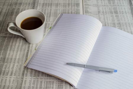 Notebook and coffee on newspaper photo