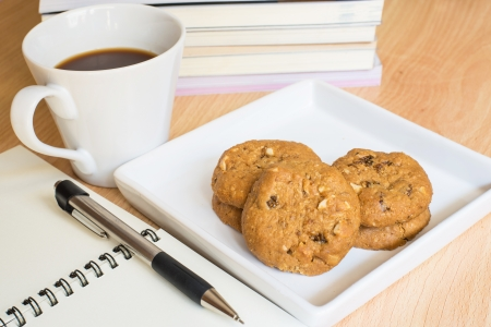 notebook and pen with coffee and cookie