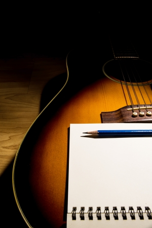 close-up Notebook and pencil on guitar,Writing music photo