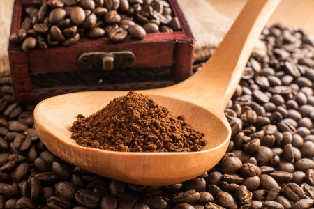 coffee grind in wooden spoon on coffee bean Stock Photo