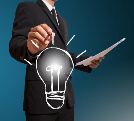 businessman drawind lamp,figure out Standard-Bild