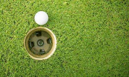 golf ball on lip of golf hole