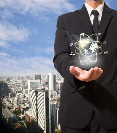 businessman with high technology in hand on top view city background