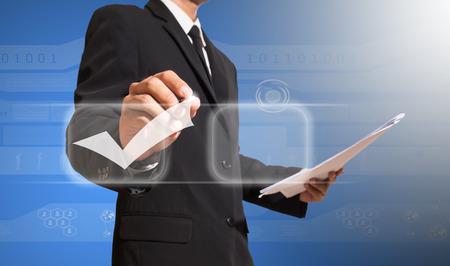 Geschäftsmann schriftlich korrekte Zeichen auf dem Bildschirm Standard-Bild - 27357328