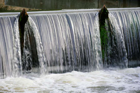 Waterfall in a river near an electrical installation