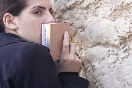 jew: Young Jewish girl in traditional clothing leaning on the Wailing Wall in Jerusalem for her prayer. Editorial