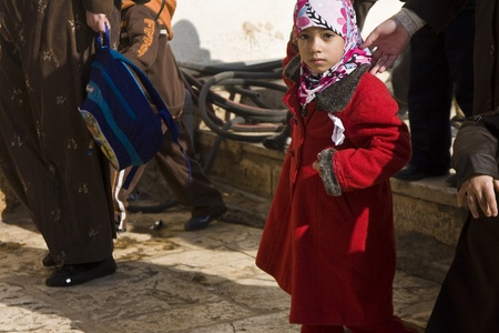 A Muslim girl watching the photographer on her way to closed school on the Mount Temple, Jerusalem.Strangers are not allowed in the area except for several hours a day, thus the mere fact of meeting a stranger is an outstanding thing for kids Stock Photo - 10006015